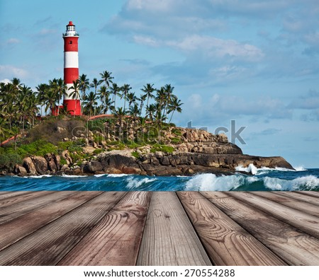 Wood planks floor with old lighthouse and sea waves in background - stock photo