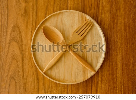Wood plate spoon fork with window light from left side - stock photo