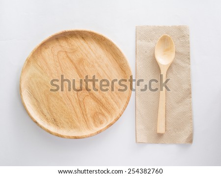 Wood plate with spoon on the table cloth - stock photo