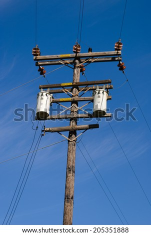 wood pole with high voltage power lines on blue sky - stock photo