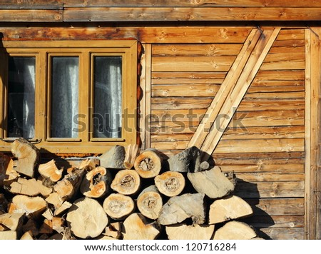 wood prepared for the fireplace near an old lodge up in the mountains - stock photo