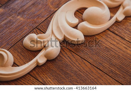 Wood processing. Joinery work. woodcarving. piece carved detail on a wooden background in perspective. close up. used as background. small depth of field