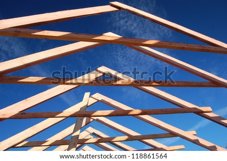 Wood Roof Trusses viewed from inside of new home looking out to a blue sky above .Ukraine - stock photo