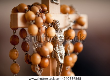 Wood rosary and Jesus figurine dangle on wooden cross, detail in horizontal orientation, nobody. - stock photo