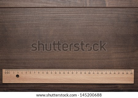 wood ruler on the brown wooden background - stock photo