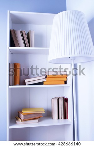 wood shelf with book. a bookcase and floor lamp. The interior of the office or at home - stock photo