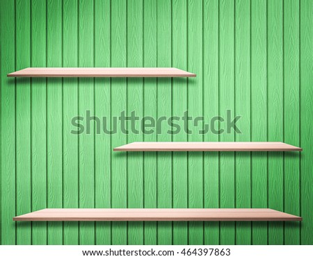 Wood shelves empty on a background of green wooden wall.