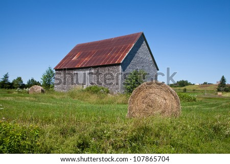Wood-shingled barn with a red rusted metal roof in New Brunswick, Canada, under a clear blue spring sky