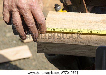 Wood siding contractor using a tape measure before cutting trim boards on the construction of a new home - stock photo