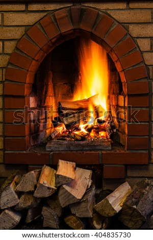 wood stack and logs burning in indoor brick fireplace in country cottage - stock photo