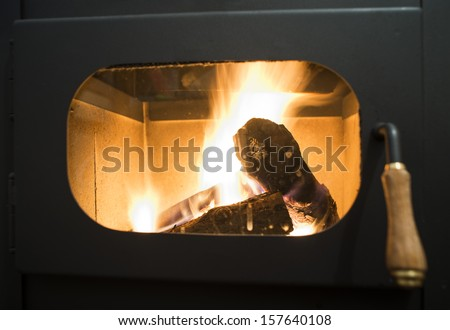 Wood stove and wood burning inside - stock photo