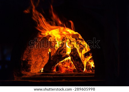 Wood stove with fire and blaze - stock photo