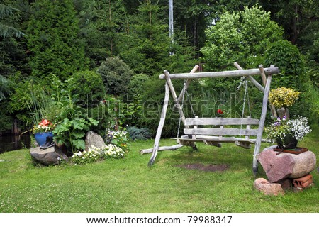 Wood swing in the green garden - stock photo