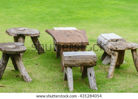 wood table and chair table on grass - stock photo
