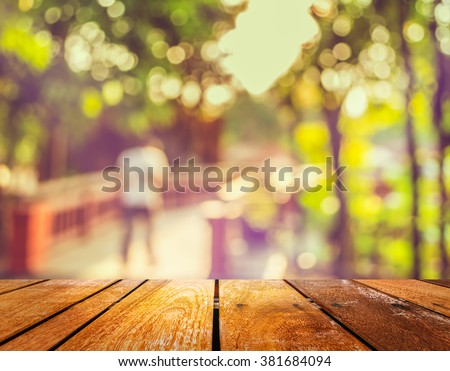 wood table and vintage tone blur image of people walking in the park  with bokeh for background usage . - stock photo