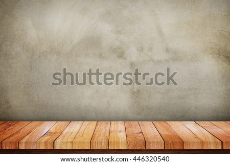 Wood table background in front of gray concrete wall, blank space for your text, design or copyspace.