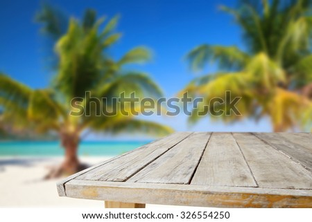 Wood table on blurred beach background - stock photo