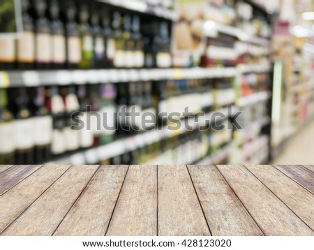 wood table over blur wine bottles on shelf in wine store, product display - stock photo