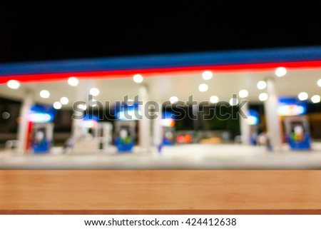 Wood table top on Abstract blur Gas station at night for background - can be used for display or montage your products - stock photo