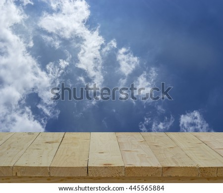 wood table top on blur background of blue sky and clouds - can use to display or montage on product - stock photo