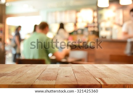 Wood table top on blur background of coffee shop interior with some people - can be used for display or montage your products - stock photo