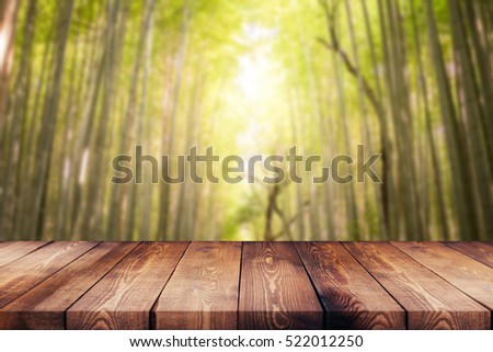 Wood table top on blur background of tree , bamboo with sunshine - can be used for display or montage your products