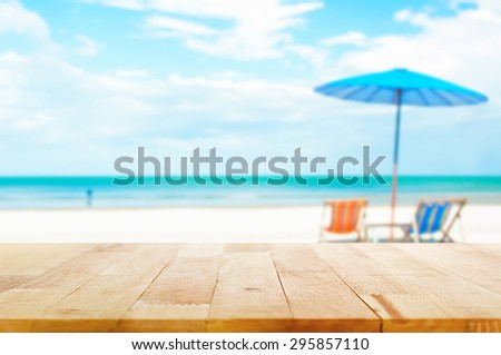 Wood table top on blur beach background with beach chairs and parasol - can be used for display or montage your products - stock photo