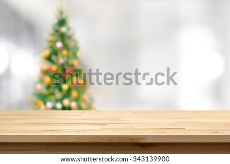 Wood table top on blur Christmas tree background - can be used for montage or display your products - stock photo