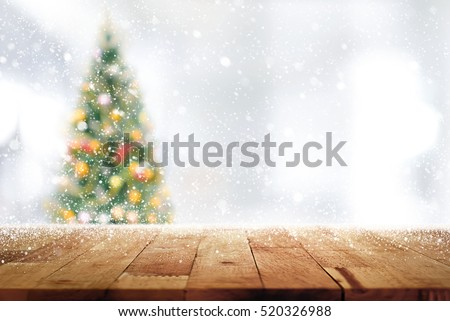 Wood table top on blur Christmas tree  in snowfall background - can be used for display or montage your products