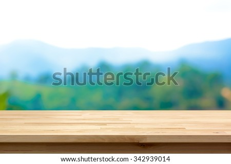 Wood table top on blur mountain background - can be used for display or montage your products - stock photo