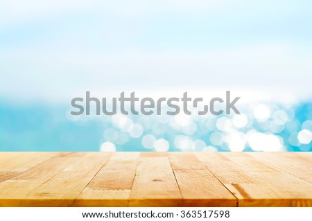 Wood table top on blur summer blue sea and sky background - can be used for display or montage your products - stock photo