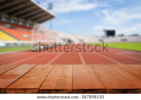 Wood table top on blurred background of Red running tracks in sport stadium  - can be used for display or montage your products - stock photo