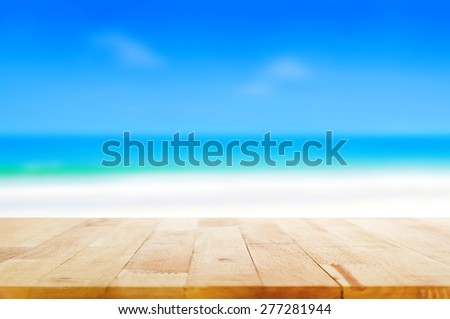 Wood table top on blurred beach background, summer concept  - can be used for display or montage your products - stock photo