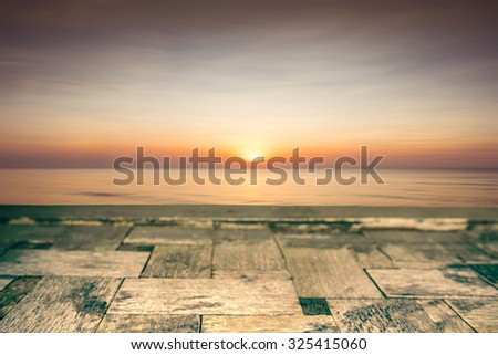 Wood table top on blurred beach sunset background, soft focus - can be used for display or montage your products - stock photo
