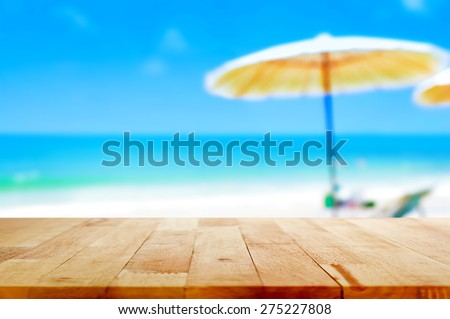 Wood table top on blurred blue sea and white sand beach background - can be used for display or montage your products - stock photo