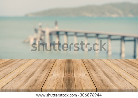 Wood table top on blurred blue sea and white sand beach background, vintage tone - can be used for display or montage your products