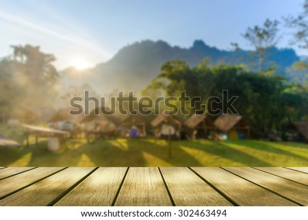 Wood table top on blurred camping in forest background - can be used for display or montage your products - stock photo