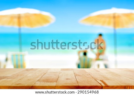 Wood table top on blurred white sand beach background with some people - can be used for montage or display your products - stock photo