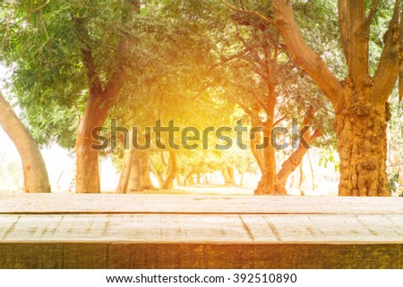 Wood table top on nature tree background with vintage light effect. can be used for display or montage your products - stock photo