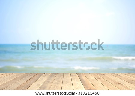 Wood table top with blurred sea as background - can be used for montage or display your products  - stock photo