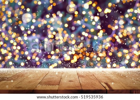 Wood Table Top With Snow And Decorative Light Bokeh On Christmas Tree At Night In Background