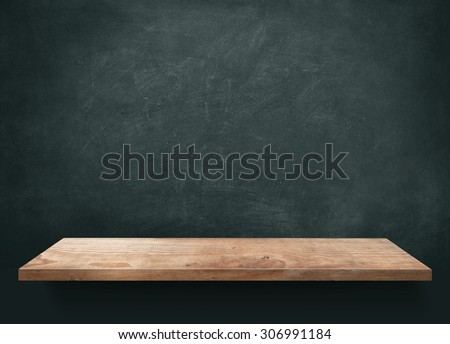 Wood table with blackboard background - stock photo