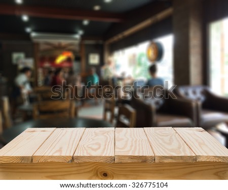 Wood table with blur coffee shop background - stock photo