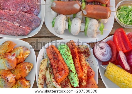 Wood Table With Different Cookout Food For Summer BBQ Grill Family Picnic Party. Beef Steaks, Mushrooms, Corn Cob, Onion, Sausages, Chicken Legs, Bell Pepper, Carrot, Potato, Kebabs, zucchini - stock photo