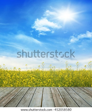 Wood table with tall grass and farmland in background