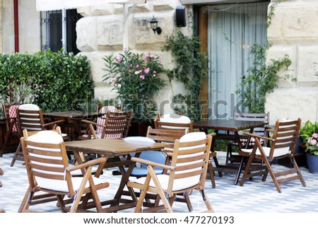 Wood tables, wood chair  and flowers at the restaurant. Restaurant exterior. Restaurant terrace.Restaurant table.Restaurant chair. Summer restaurant.