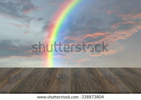 Wood terrace and Red sky and storm cloud with rainbow - stock photo