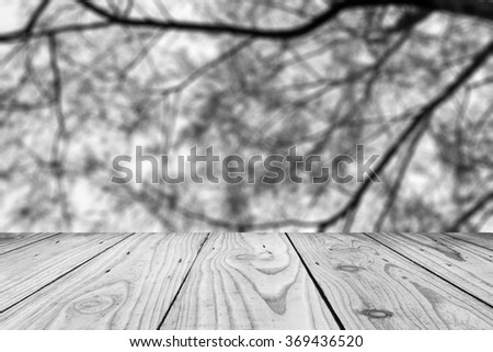 Wood terrace with blurred image branch of tree: black and white tone - stock photo