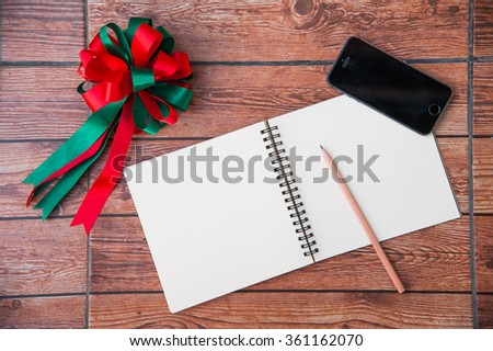 Wood texture mock up with notebook, ribbon, smart phone and pencil. View from above.Create a card for Christmas Day. - stock photo