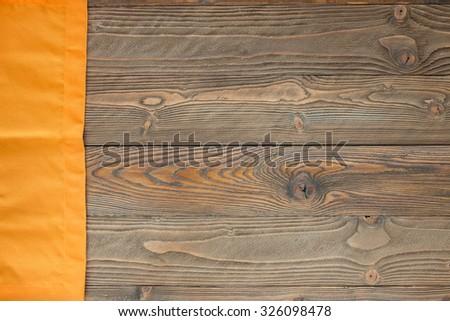 wood texture with orange textile napkin, top view, horizontal - stock photo